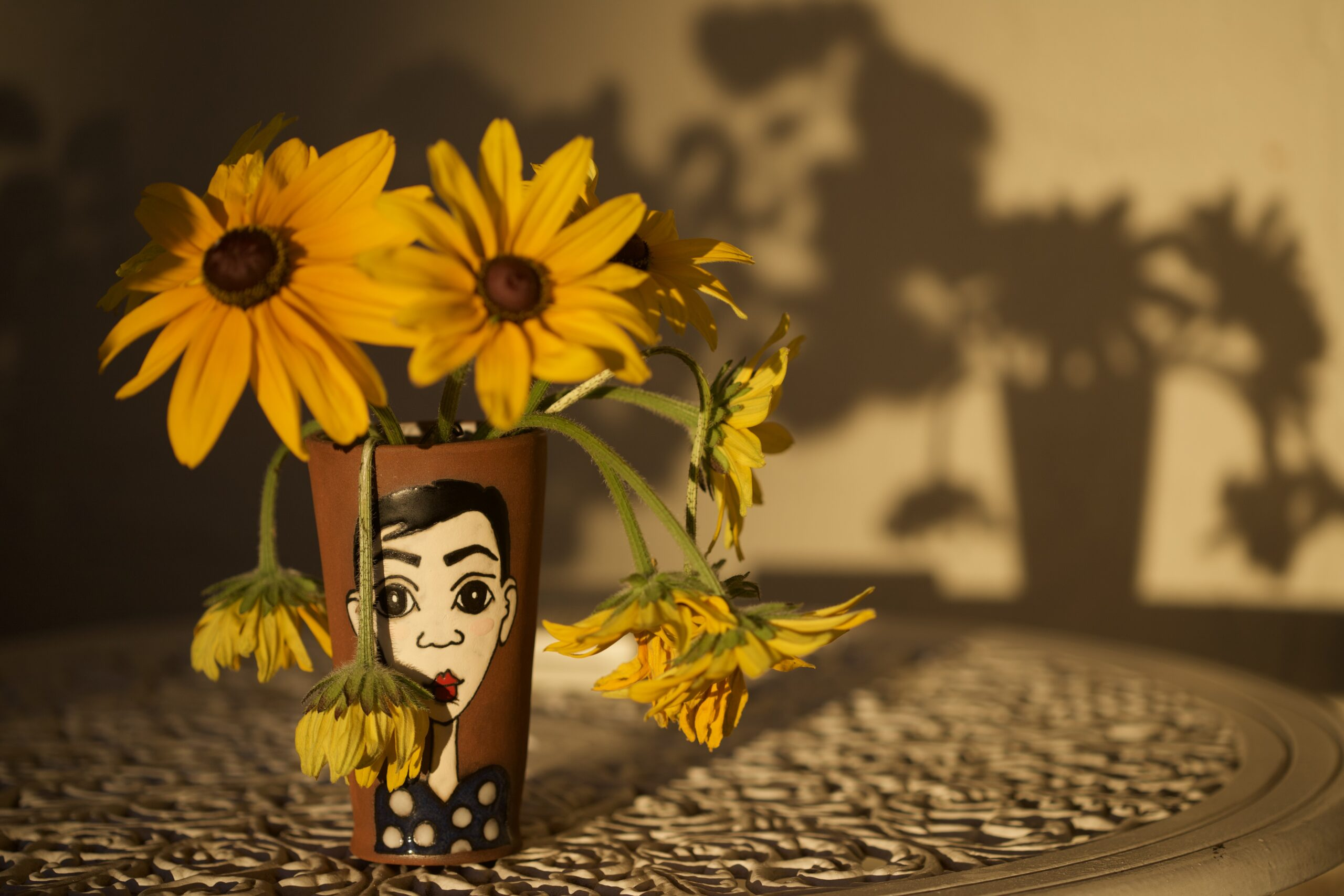 Sunflowers in painted vase casting a shadow on a yellow wall