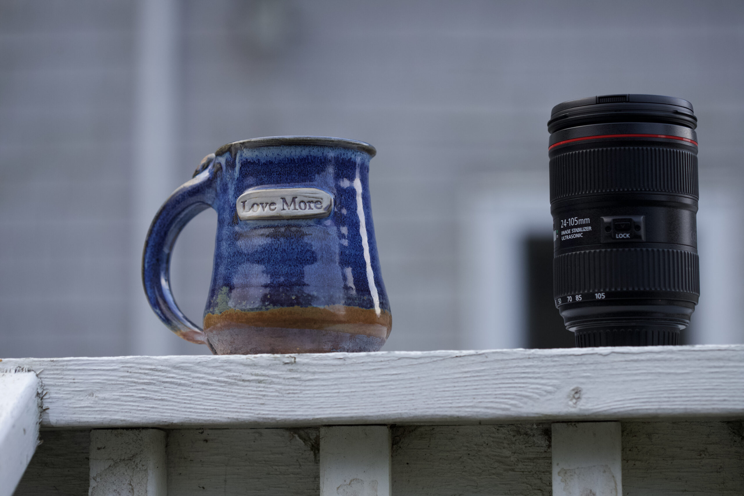 """Blue handcrafted mug with words """"love more"""" engraved on it sitting next to a DLSR camera lens"""